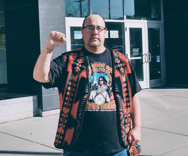 Steve Martinez raises fist in front of Federal Courthouse in Bismark, ND, 2021