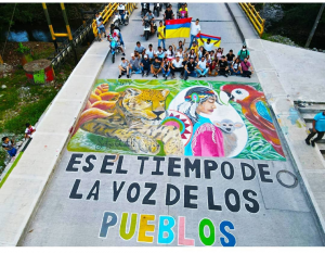 """Photo of a street mural with nature themes reading, in Spanish, """"This is the Time of the voice of the Communities"""""""