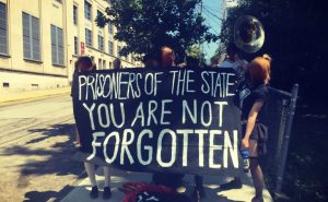 """An anti-prison protest in Pittsburgh with people holding musical instruments and a banner reading """"Prisoners of the state: you are not forgotten"""""""