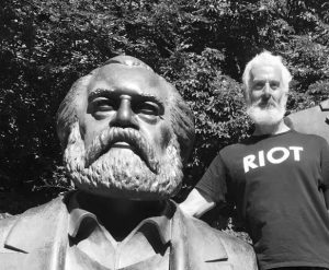 """Joshua Clover with a beard and shirt reading """"Riot"""" next to a statue of Karl Marx"""
