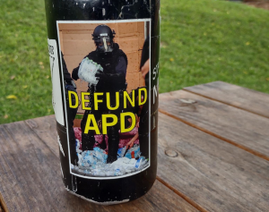 """""""Defund APD"""" sticker on a water bottle, depicting an asheville police officer stabbing and crushing water bottles after raiding a medic table during George Floyd protests in 2020. Based on a photo by Angie Wilhelm"""